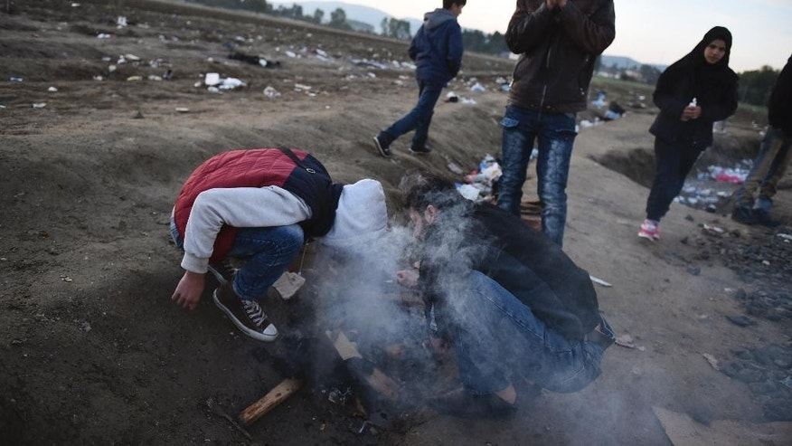 Migrants and refugees light a fire as they wait to pass from the northern Greek village of Idomeni to southern Macedonia Monday, Oct. 26, 2015.European leaders decide that reception capacities should be boosted in Greece and along the Balkans migration route to accommodate 100,000 more people as winter looms. (AP Photo/Giannis Papanikos)