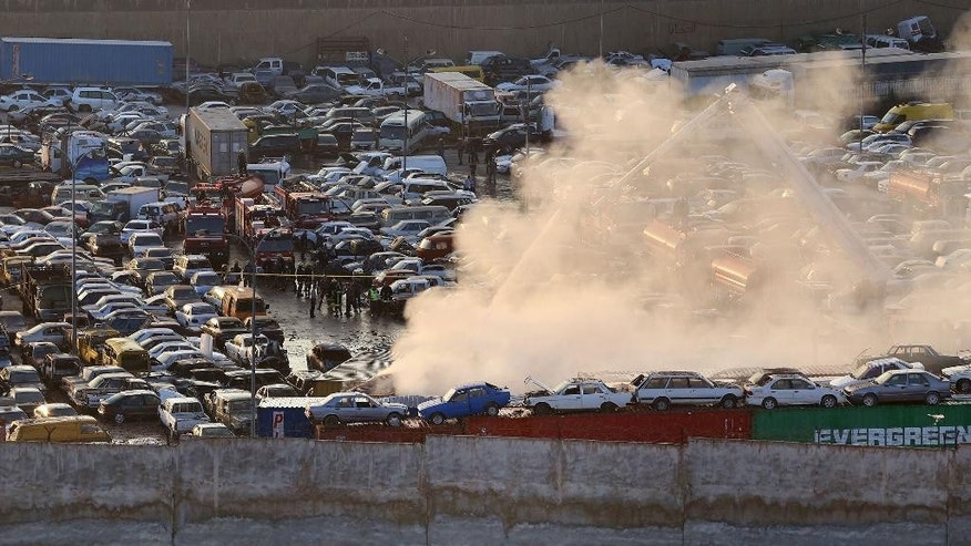 Smoke rises at the site after two containers filled with fireworks exploded, in Amman, Jordan, Monday, Oct. 26, 2015. Two containers filled with fireworks exploded at a customs storage area in Jordan's capital of Amman on Monday, killing many people and wounding at least 9, several critically, a civil defense official said. (AP Photo/Raad Adayleh)