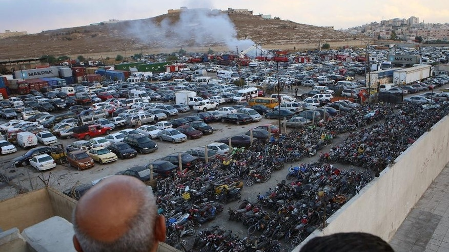 People look at smoke leaping the air at the site after two containers filled with fireworks exploded, in Amman, Jordan, Monday, Oct. 26, 2015. Two containers filled with fireworks exploded at a customs storage area in Jordan's capital of Amman on Monday, killing many people and wounding at least 9, several critically, a civil defense official said. (AP Photo/Raad Adayleh)