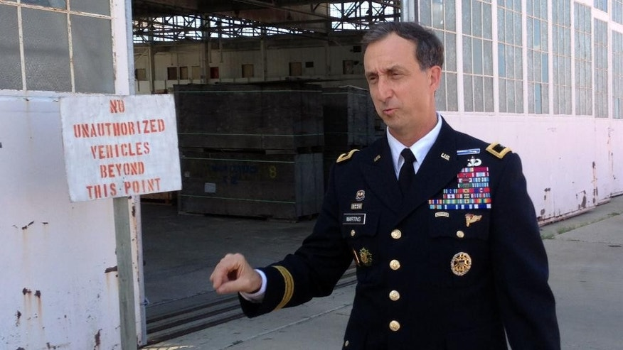 """In this Friday, Oct. 23, 2015 photo, U.S. Army Brig. Gen. Mark Martins, the chief prosecutor at the U.S. military commission at Guantanamo Bay, Cuba, speaks to journalists and Colleen Kelly, the sister of a man killed in the Sept. 11 terrorist attack on the World Trade Center, during a break in pretrial proceedings for five men charged with planning and aiding the attack. Martins says that a great deal of work providing evidence to the defense is going on despite the slow progress in court and that delays are just part of the process. """"The judge is working according to the law and rules of procedure, not any specific schedule. And the law may compel him to suspend or stop or recess as we have been."""" (AP Photo/Ben Fox)"""