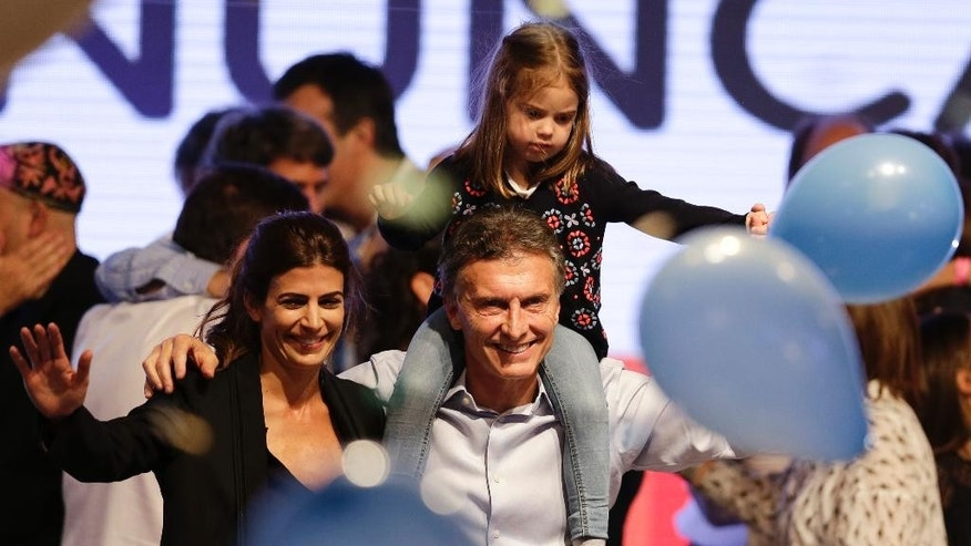 Lead opposition candidate Mauricio Macri, center, carries his daughter Antonia on his shoulders next to his wife Juliana Awada, left, in Buenos Aires, Argentina,  Sunday, Oct. 25, 2015. In a surprise that every national poll failed to anticipate, opposition Mauricio Macri was leading in Argentina's presidential elections in a race that pitted him against Scioli, the successor of President Cristina Fernandez. With 67 percent of polling places reporting, Macri had 36 percent of the vote compared to 34 percent for Scioli.  (AP Photo/Victor R. Caivano)