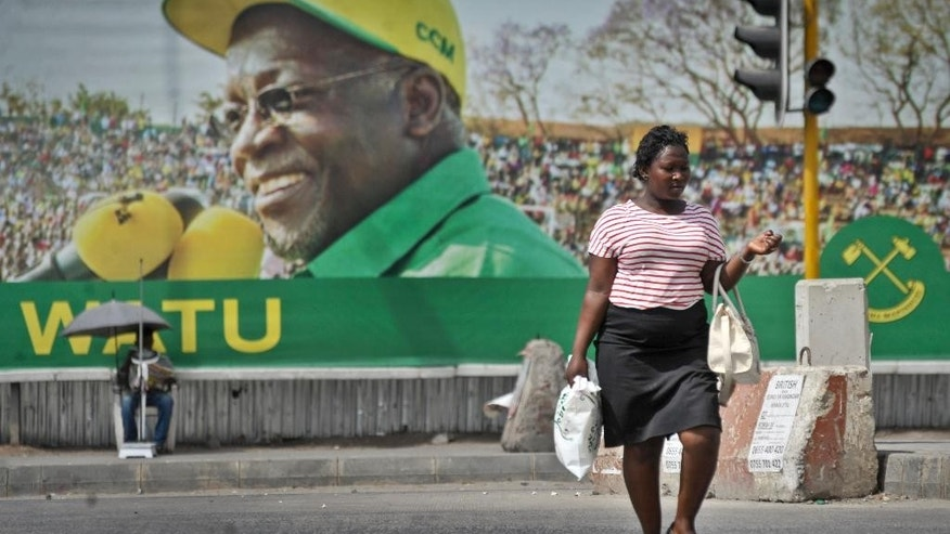 A Tanzanian woman walks past a billboard for the ruling party's presidential candidate John Magufuli, in Dar es Salaam, Tanzania Monday, Oct. 26, 2015. Tanzanians turned out in large numbers Sunday to vote in general elections in which the ruling party, in power for decades, faces a strong challenge from a united opposition, with the ruling party's candidate John Magufuli battling former Prime Minister Edward Lowassa, in a presidential race many analysts say is too close to predict. (AP Photo/Khalfan Said)