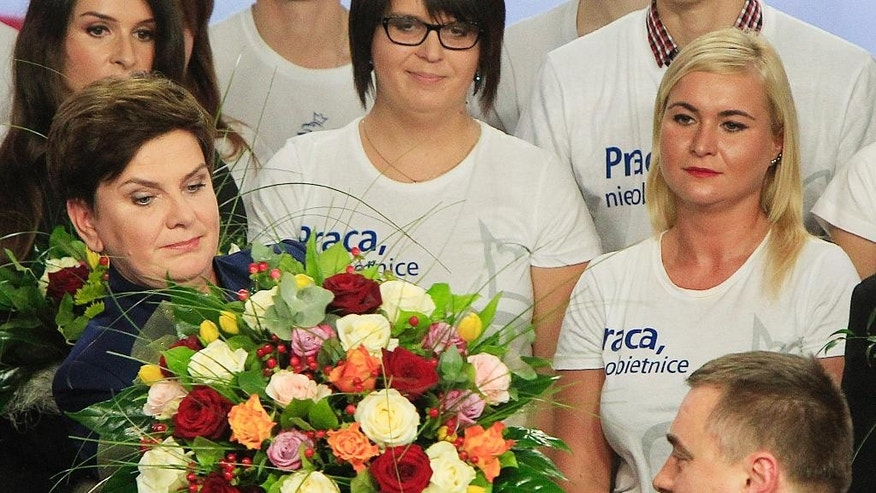 Conservative Law and Justice  candidate for the Prime Minister Beata Szydlo, left, receives flowers at the party's headquarters in Warsaw, Poland, on Sunday, Oct.25, 2015. The victory of his Eurosceptic party ends eight years in power of pro-EU, pro-business Civic Platform which voters accuse of being conformist, detached and focused on power rather than on improving the living in Poland.(AP Photo/Czarek Sokolowski)