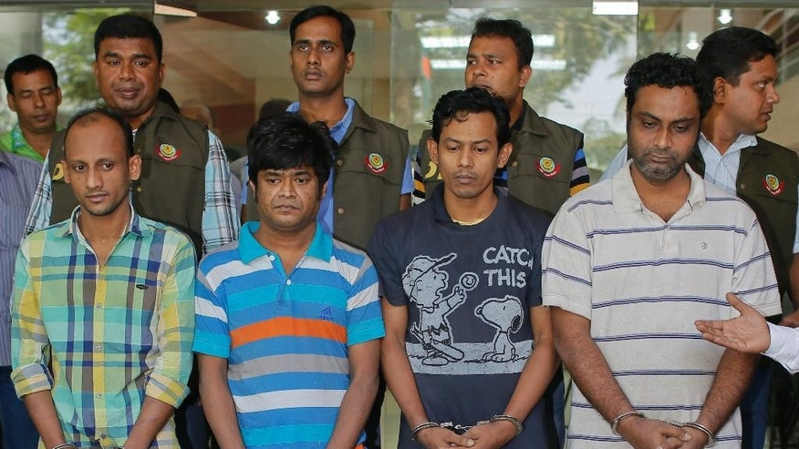 "Bangladesh police personnel, standing behind, present before media four suspects they arrested in the killing of an Italian aid worker last month, in Dhaka, Bangladesh, Monday, Oct. 26, 2015. Italian aid worker Cesare Tavella was gunned down by motorcycle-riding assailants on Sept. 28 while jogging in the diplomatic quarter of Dhaka, Bangladesh's capital. Police said Monday that the alleged gunmen had confessed to being hired to attack ""a white man"" in order to destabilize the impoverished South Asian nation. (AP Photo/ A.M. Ahad)"