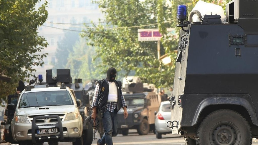 A masked police officer walks as armoured police vehicles block a road leading to the site of armed clashes with militants in Diyarbakir, southeastern Turkey, Monday, Oct. 26, 2015.  Police raided a house used by a suspected cell of the Islamic State group triggering a clash that killed up to seven militants and two policemen, Turkish media reports said. It was not immediately clear if the operation was linked to suicide bombings of a peace rally in the capital Ankara earlier this month that killed 102 people. (AP Photo/Mahmut Bozarslan)