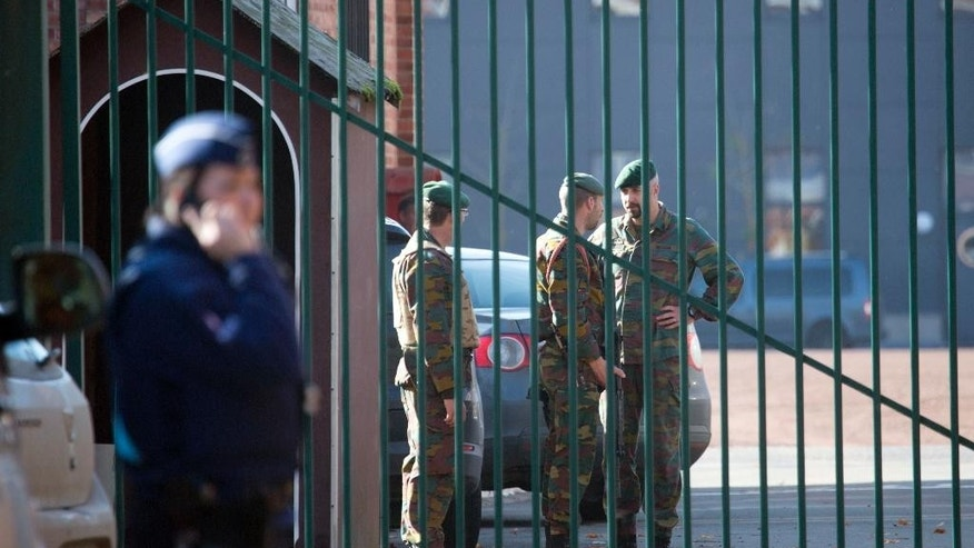 Police and military personnel stand outside a military barracks in Flawinne, Belgium on Monday, Oct. 26, 2015. Belgian media are reporting a car has attempted to crash through the gates of an army barracks and that shots have been fired. (AP Photo/Virginia Mayo)