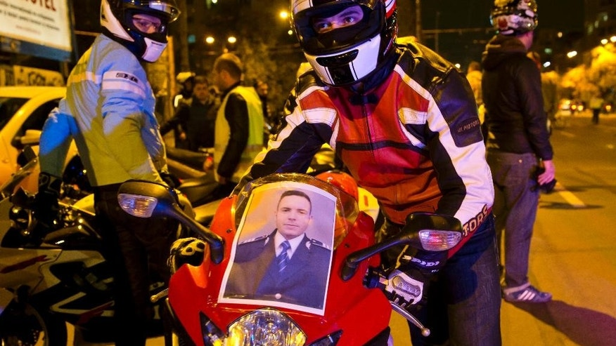 In this photo taken late Saturday, Oct. 24, 2015, a photo of killed police motorcyclist Bogdan Gigina, is placed in the windshield of a motorcycle during a solidarity drive by more than 300 bikers in Bucharest, Romania. Romania's president Klaus Iohannis has called on the prime minister and interior minister on Sunday, Oct. 25, 2015 to address public anger over the death of a police motorcyclist who died during a traffic mission after hitting a large hole in the road while escorting Interior Minister Oprea. (AP Photo/Vadim Ghirda)
