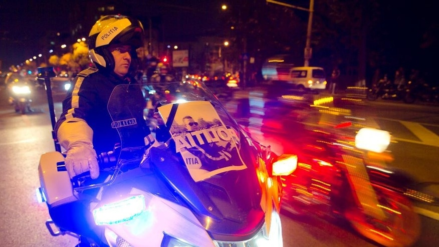 In this photo taken late Saturday, Oct. 24, 2015, a photo of killed police motorcyclist Bogdan Gigina, is placed in the windshield of a colleague's motorcycle during a solidarity drive by more than 300 bikers in Bucharest, Romania. Romania's president Klaus Iohannis has called on the prime minister and interior minister on Sunday, Oct. 25, 2015 to address public anger over the death of a police motorcyclist who died during a traffic mission after hitting a large hole in the road while escorting Interior Minister Oprea. (AP Photo/Vadim Ghirda)