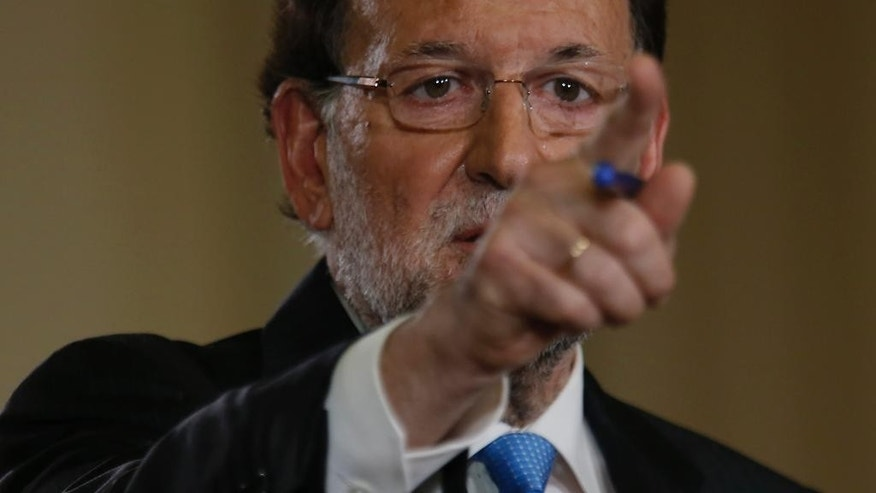 Spanish Prime Minister Mariano Rajoy gestures as he talks to journalists during a news conference following a cabinet meeting at the Moncloa palace, the premier's official resident, in Madrid, Monday, Oct. 26, 2015. Rajoy on Monday signed a decree formally dissolving Parliament and calling general elections Dec. 20, using the occasion to do some campaigning by praising his government's handling of the severe economic crisis. (AP Photo/Francisco Seco)