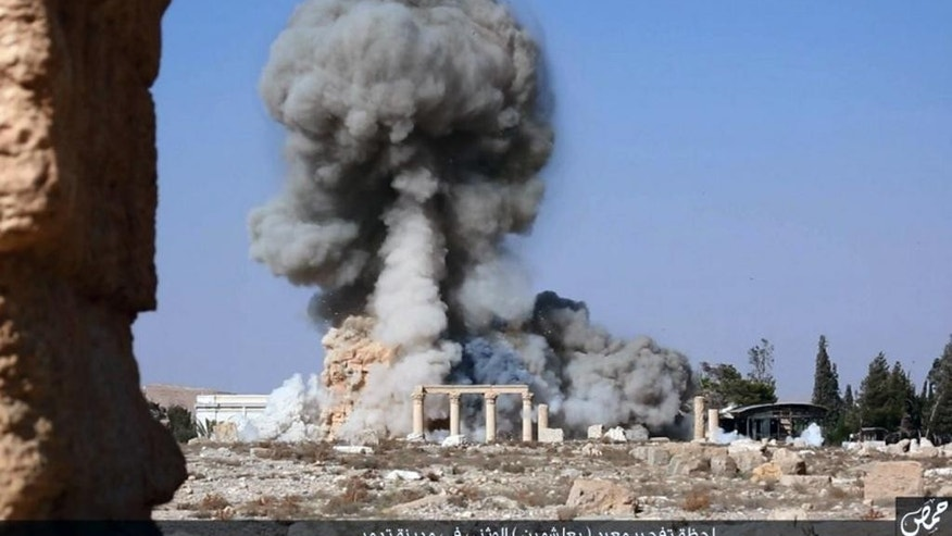 FILE - This undated photo released Tuesday, Aug. 25, 2015, file photo, on a social media site used by Islamic State militants, which has been verified and is consistent with other AP reporting, shows smoke from the detonation of the 2,000-year-old temple of Baalshamin in Syria's ancient caravan city of Palmyra. Activists say the Islamic State group in has killed three captives on Monday, Oct. 26, 2015 in Syria's ancient city of Palmyra by tying them to Roman-era columns at the site, then blowing the structures up with explosives. (Islamic State social media account via AP, File)