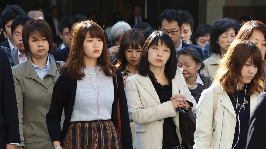 In this Monday, Oct. 26, 2015 photo, commuters cross a street during morning rush hour in Tokyo. The central government exceeded its 30 percent target for hiring of women for career-track positions, raising the rate to 34 percent this year from 24 percent last year, according to the latest Cabinet Office data. Two years after Prime Minister Shinzo Abe made women's advancement a top policy priority, statistics suggest Japan's male-dominated workplaces have evolved slightly, but also highlight the deep-seated societal forces keeping the gender gap alive. (AP Photo/Koji Sasahara)
