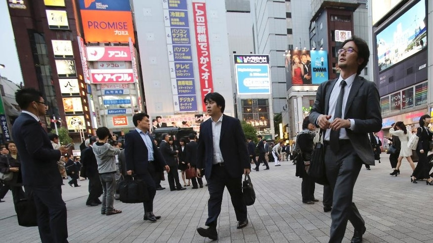 In this Oct. 23, 2015 photo, businessmen walk through a square in Tokyo. Two years after Prime Minister Shinzo Abe made women's advancement a top policy priority, statistics suggest Japan's male-dominated workplaces have evolved slightly, but also highlight the deep-seated societal forces keeping the gender gap alive. (AP Photo/Koji Sasahara)