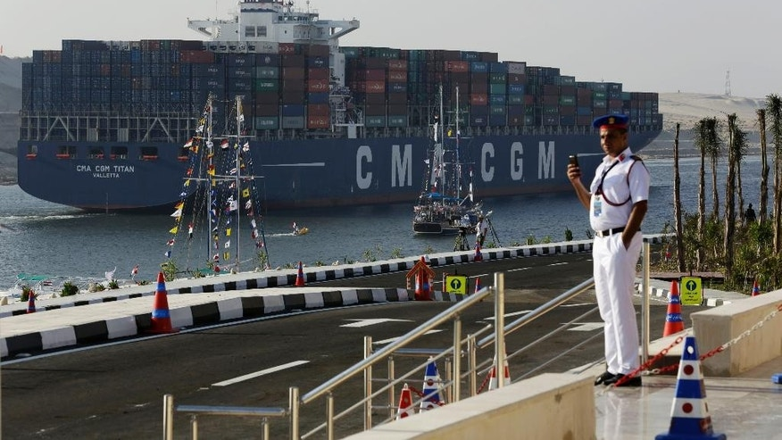 FILE - In this Thursday, Aug. 6, 2015 file photo, a cargo container ship crosses the new section of the Suez Canal after the opening ceremony in Ismailia, Egypt. Toll revenues for Egypt's Suez Canal fell in September 2015, dampening hopes that a new parallel waterway -- which authorities claimed would more than double canal income in the next seven years -- will boost the economy in the immediate future. Data released on Monday, Oct. 25, 2015, by canal authorities shows that monthly revenue was $448.8 million in September, down some $13 million from the previous month. (AP Photo/Hassan Ammar, File)