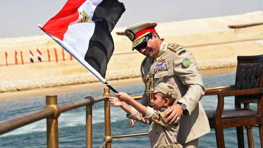 FILE -- In this Aug. 6, 2015 file photo, provided by the office of the Egyptian Presidency, Egyptian President Abdel-Fattah el-Sissi smiles at a boy dressed in a military uniform and waving the national flag  during a ceremony unveiling a major extension of the Suez Canal in Ismailia, Egypt. Toll revenues for Egypt's Suez Canal fell in September 2015, dampening hopes that a new parallel waterway -- which authorities claimed would more than double canal income in the next seven years -- will boost the economy in the immediate future. (Egyptian Presidency, File via AP) MANDATORY CREDIT