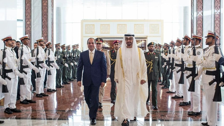 In this photo made available by Emirates News Agency, WAM, Sheikh Mohamed bin Zayed Al Nahyan, Crown Prince of Abu Dhabi and Deputy Supreme Commander of the UAE Armed Forces, right, receives Abdel-Fattah El-Sisi President of Egypt at The Presidential Airport in Abu Dhabi, United Arab Emirates. (Ryan Carter, Crown Prince Court via AP)