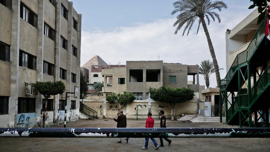 Egyptian election workers arrive inside a polling center before polls open, during the runoff to the first round of the parliamentary election, in Al-Haram in Giza, a neighboring city of Cairo, Egypt, Tuesday, Oct. 27, 2015. The Great Giza Pyramid is seen at background left. (AP Photo/Nariman El-Mofty)