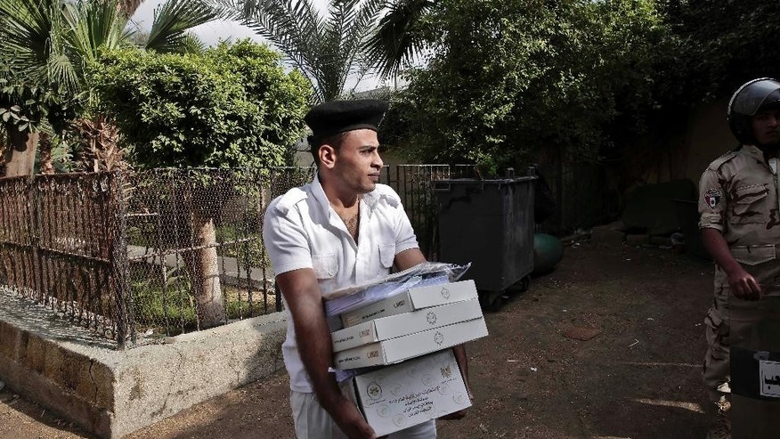An Egyptian policeman carries boxes with ballots inside a polling center before the polls open, during the runoff to the first round of the parliamentary election, in Al Haram in Giza, a neighboring city of Cairo, Egypt, Tuesday, Oct. 27, 2015. (AP Photo/Nariman El-Mofty)