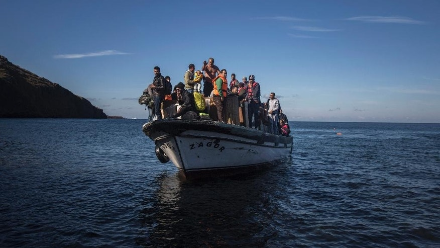 A wooden boat with around 120 refugees from Syria and Iraq approaches the shores of the Greek island of Lesbos after crossing the Aegean sea from Turkey, on Monday, Oct. 26, 2015. Greece's government says it is preparing a rent-assistance program to cope with a growing number of refugees, who face the oncoming winter and mounting resistance in Europe. (AP Photo/Santi Palacios)