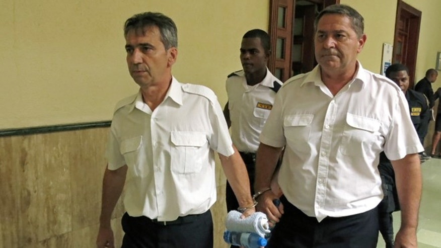 French pilots Bruno Odos and Pascal Jean Fauret escorted to a courtroom in Santo Domingo on June 17, 2014.