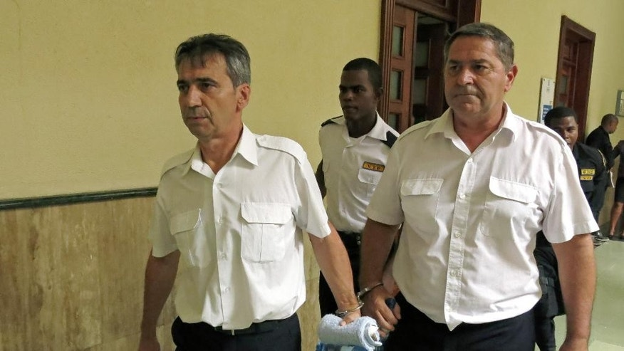 FILE - In this June 17, 2014 file photo, French pilots Bruno Odos, left, and Pascal Jean Fauret, who have been formally charged with drug trafficking, are escorted to a courtroom in Santo Domingo, Dominican Republic. The two French pilots convicted to 20 years in prison for cocaine trafficking fled house arrest and have returned to France, their lawyer says Tuesday, Oct.27, 2015. The French government insisted it didn't have anything to do with the daring and unusual escape. (AP Photo/Ezequiel Abiu Lopez, File)