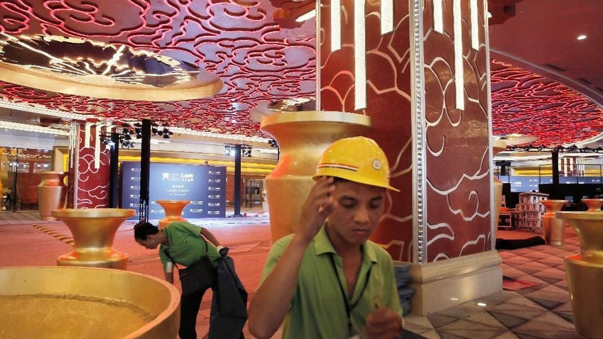 In this Monday, Oct. 26, 2015, photo, workers put the final touches at the Melco Crown Entertainment Ltd.'s $3.2 billion Studio City project one day before the grand opening in Macau, China. China's world-beating gambling hub is getting a taste of Hollywood glamor as its newest casino resort makes its debut on Tuesday with a glitzy grand opening that hides turmoil behind the scenes. (AP Photo/Vincent Yu)