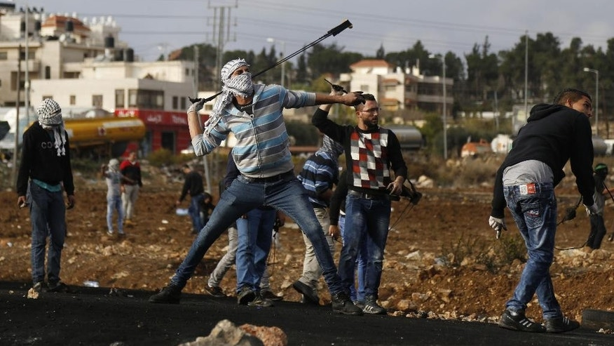 A Palestinian swings a sling during clashes with Israeli troops near Ramallah, West Bank, Tuesday, Oct. 27, 2015. (AP Photo/Majdi Mohammed)