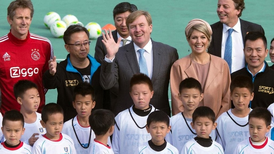 Dutch King Willem-Alexander, center, waves next to his wife Queen Maxima as they pose for photos with Chinese children and Dutch goalkeeper Edwin Van Der Sar,  left, during a football event at the Shijia School in Beijing, China, Sunday, Oct. 25, 2015. (AP Photo/Ng Han Guan)