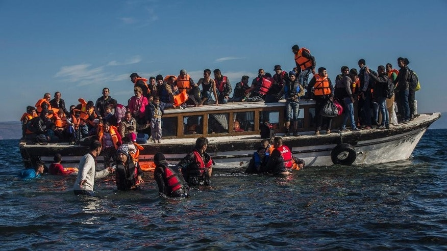 Refugees from Syria and Iraq disembark on the Greek island of Lesbos after arriving with 120 other refugees on a wooden boat from the Turkish coast, Monday, Oct. 26, 2015. Greece's government says it is preparing a rent-assistance program to cope with a growing number of refugees, who face the oncoming winter and mounting resistance in Europe. (AP Photo/Santi Palacios)