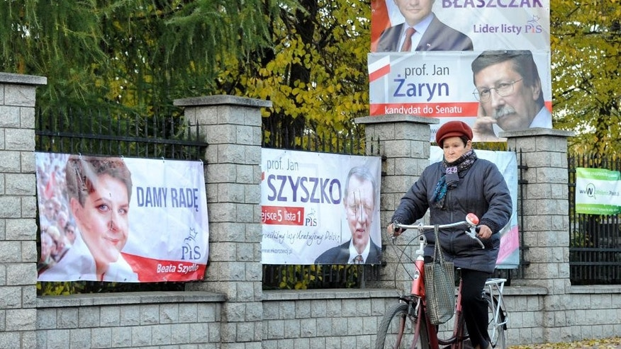 A cyclist drives past Law and Justice election posters, among them Beata Szydlo's first left, in Warsaw, Poland, Monday, Oct. 26, 2015. The conservative Law and Justice Party, which won Poland's general elections, has tapped Szydlo to become the nation's next prime minister, the second woman in a row to hold the post. (AP Photo/Alik Keplicz)