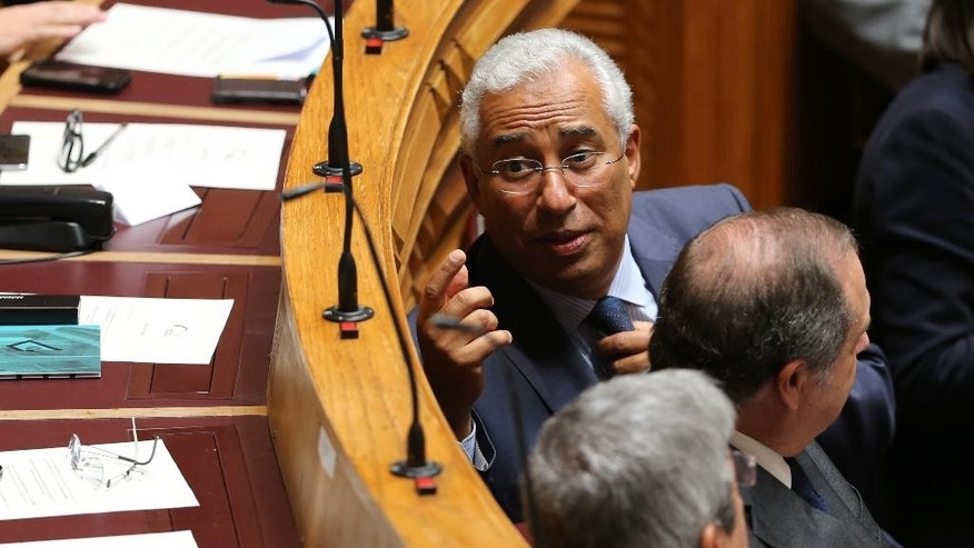 "Antonio Costa, left, leader of the Portuguese Socialist Party, chats with members of parliament during the national assembly's first session, Friday, Oct. 23, 2015, following the Oct. 4 general elections.  Costa, who has been negotiating the creation of a left-of-center majority government, accused President Anibal Cavaco Silva of triggering ""a pointless political crisis"" by inviting Incumbent Prime Minister Pedro Passos Coelho to form a minority government. (AP Photo/Armando Franca)"