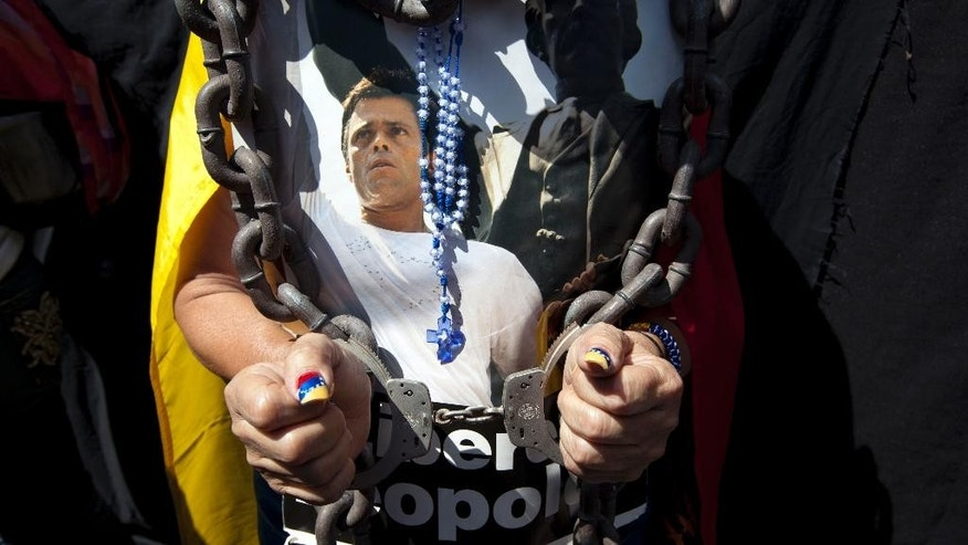 FILE - In this Feb. 18, 2015 file photo, a woman wearing handcuffs, chains and a rosary holds a poster of jailed opposition leader Leopoldo Lopez at an event marking the one year anniversary of his arrest and imprisonment in Caracas, Venezuela. Prosecutor Franklin Nieves, who reportedly is now seeking asylum in the United States, said in a video posted Monday, Oct. 26, 2015 on the Venezuelan news website La Patilla that superiors in the prosecutor's office had given him orders to have Lopez arrested days before the Caracas protest - and the alleged crime - took place. Lopez was convicted in September 2015 of inciting violence during a 2014 anti-government protest in Caracas and received the maximum sentence, about 14 years.  (AP Photo/Ariana Cubillos, File)