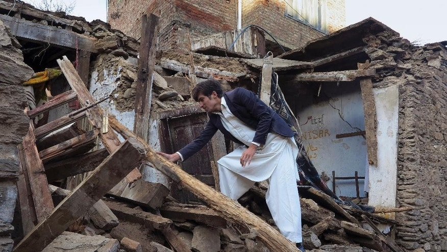 A Pakistani boy examines a house damaged caused by massive earthquake in Mingora, the main town of Swat valley, Tuesday, Oct. 27, 2015. Officials say rescuers are struggling to reach quake-stricken regions in Pakistan and Afghanistan. (AP Photo/Naveed Ali)