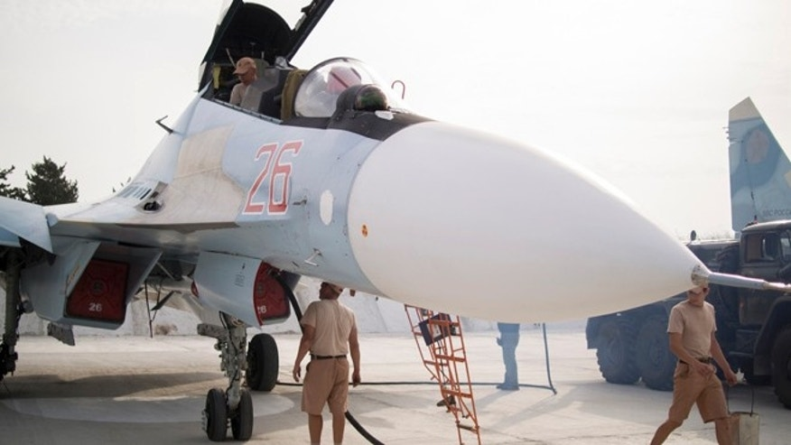 Oct. 22, 2015: Russian air force technicians service a Russian fighter jet at Hemeimeem airbase, Syria.