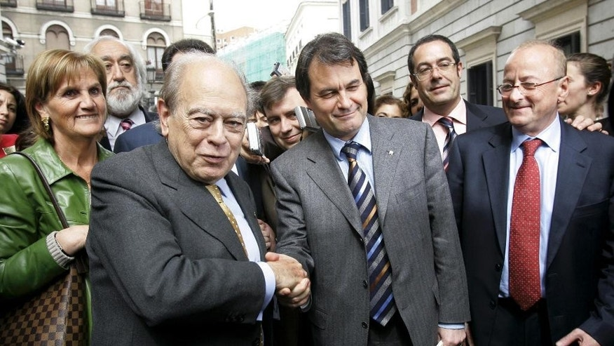 FILE - In this March 30, 2006 file photo, former president of the Catalonian autonomous government and member of the Convergence and Union Party (CiU), Jordi Pujol, left, shakes hands with Artur Mas, leader of CiU in Madrid, Spain. Spanish police on Tuesday Oct. 27, 2015 raided more than a dozen houses and offices of the family of Jordi Pujol, former longtime leader of Spain's Catalonia region, in a money-laundering and tax fraud probe. Pujol, 85, founded Catalonia's Convergence party that governs the economically powerful region. He was the region's president from 1980 to 2003 and is considered the father of the Catalan nationalist movement. His house was one of those searched Tuesday. (AP Photo/Bernat Armangue, File)
