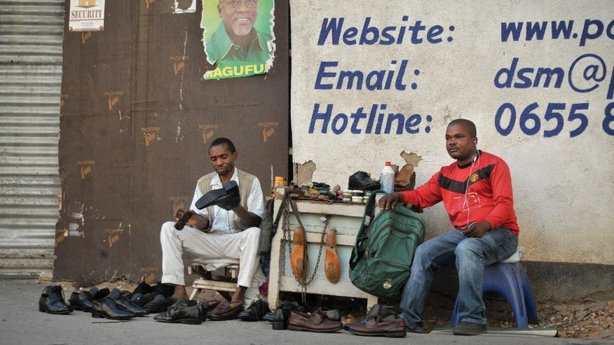A Tanzanian shoe-shiner conducts his business underneath an election poster for ruling party presidential candidate John Magufuli, in Dar es Salaam, Tanzania Tuesday, Oct. 27, 2015. The presidential race is the most tightly contested since Tanzania became independent in 1961, with the ruling party being challenged by a former member who was recently the country's prime minister. (AP Photo/Khalfan Said)