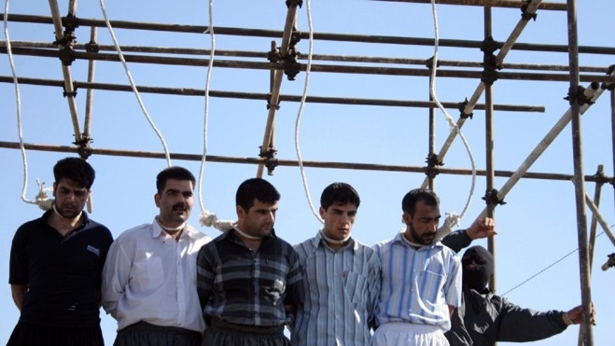 2007: A policeman prepares five men, convicted of various charges including rape, for their hanging in Iran.