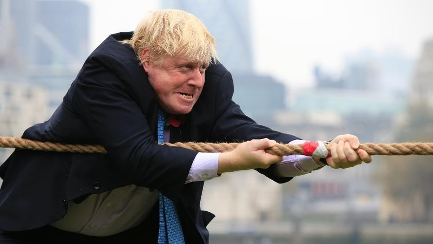Mayor of London Boris Johnson in action during a tug-of-war contest with personnel from the Royal Navy, the Army and the Royal Air Force at the launch of London Poppy Day, on Potters Field, next to City Hall in London, Tuesday Oct. 27, 2015.  The Poppy Day appeal raises money to support service personnel and their families, by remembering those who have given their lives from all nations in military conflicts. (Jonathan Brady / PA via AP) UNITED KINGDOM OUT - NO SALES - NO ARCHIVES