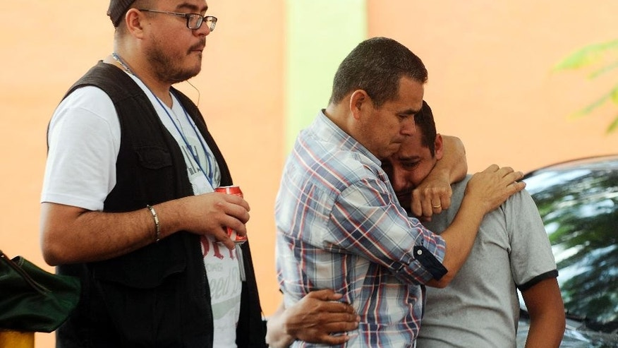 Ivan Rosales, center, comforts his co-worker Javier Servellon as Joel Funez looks down, outside the Diario Tiempo newspaper in Tegucigalpa, Honduras, Tuesday, Oct. 27, 2015. The Honduran newspaper Tiempo says it is temporarily closing after the government seized businesses belonging to the paper's owners, who are accused in the United States of money laundering. Tiempo has published for 45 years. (AP Photo/Fernando Antonio)