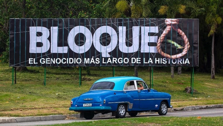 "A classic American car used as a taxi passes a billboard that reads in Spanish: ""Blockade, the longest genocide in history"" in Havana, Cuba, Tuesday, Oct. 27, 2015. The United States on Tuesday voted against a U.N. resolution condemning its embargo on Cuba, despite President Barack Obama's calls on Congress to lift the trade restrictions. (AP Photo/Desmond Boylan)"