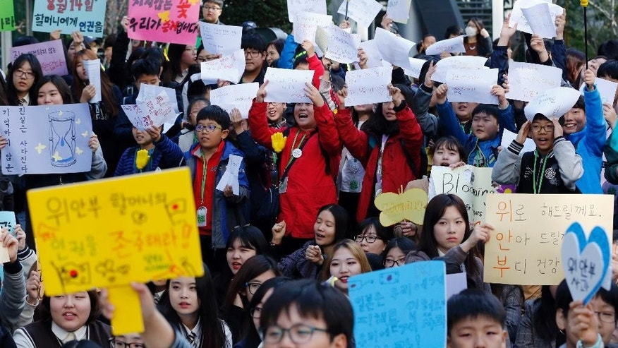 "South Korean students hold signs during a rally demanding full compensation and apology for wartime sex slaves from Japanese government near the Japanese Embassy in Seoul, South Korea, Wednesday, Oct. 28, 2015. Only days before leaders from South Korea, Japan and China are to gather in Seoul this weekend, the event has still not yet been formally settled, with the South Korean and Japanese foreign ministries publicly dodging questions even as diplomats leak barbed tidbits to reporters behind the scenes. The problem this week, as is often the case in Northeast Asia, appears to be history, and specifically the inability of Seoul and Tokyo to settle disputes stemming from Japan's brutal colonial rule of Korea in the early 20th century. The letters read ""Apology and Live long and stay healthy."" (AP Photo/Lee Jin-man)"