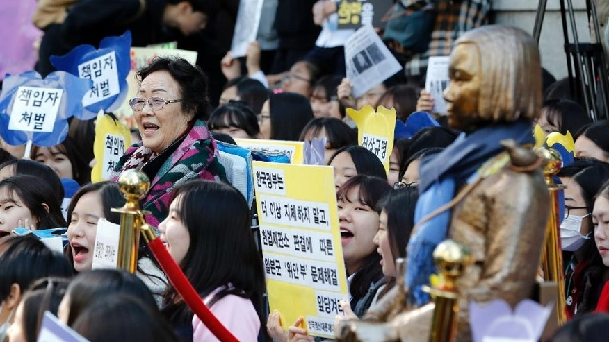 "Lee Yong-soo, left, who was forced by the Japanese government to serve as a sexual slave during World War II, shouts slogans with students near the statue symbolizing ""a wartime sex slave"" during a rally demanding full compensation and apology for wartime sex slaves from Japanese government near the Japanese Embassy in Seoul, South Korea, Wednesday, Oct. 28, 2015. Only days before leaders from South Korea, Japan and China are to gather in Seoul this weekend, the event has still not yet been formally settled, with the South Korean and Japanese foreign ministries publicly dodging questions even as diplomats leak barbed tidbits to reporters behind the scenes. The problem this week, as is often the case in Northeast Asia, appears to be history, and specifically the inability of Seoul and Tokyo to settle disputes stemming from Japan's brutal colonial rule of Korea in the early 20th century. (AP Photo/Lee Jin-man)"