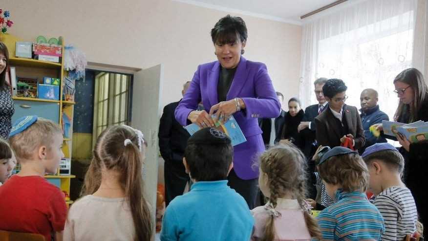 U.S. Commerce Secretary Penny Pritzker presents books to children in a Jewish school  in the Ukrainian town of Bila Tserkva, where some of her distant relatives once lived in Ukraine, Tuesday, Oct. 27, 2015. (AP Photo/Efrem Lukatsky)