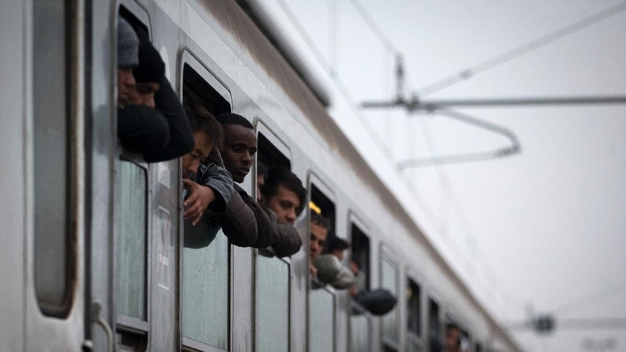 Migrants look out from a train that brought them from Croatia, in Dobova, Slovenia, Tuesday, Oct. 27, 2015. The European Union is lashing member countries for dragging their feet on providing funds and experts to help manage Europe's biggest refugee emergency in decades. (AP Photo/Darko Bandic)