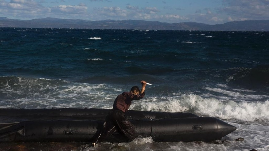 Afghan migrant uses a knife to puncture the dinghy in which he crossed with others from Turkey to the Greek island of Lesbos, Wednesday, Oct. 28, 2015. Greece's government says it is preparing a rent-assistance program to cope with a growing number of refugees, who face the oncoming winter and mounting resistance in Europe. (AP Photo/Santi Palacios)