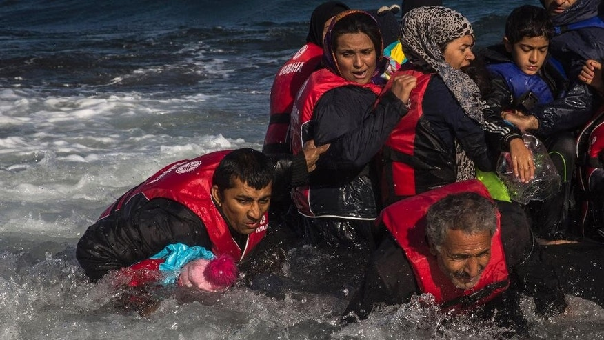 A group of Afghan migrants, including a small child carried through the water by man at left, disembark safely from their frail boat in bad weather on the Greek island of Lesbos after crossing the Aegean see from Turkey, Wednesday, Oct. 28, 2015. Greece's government says it is preparing a rent-assistance program to cope with a growing number of refugees, who face the oncoming winter and mounting resistance in Europe. (AP Photo/Santi Palacios)