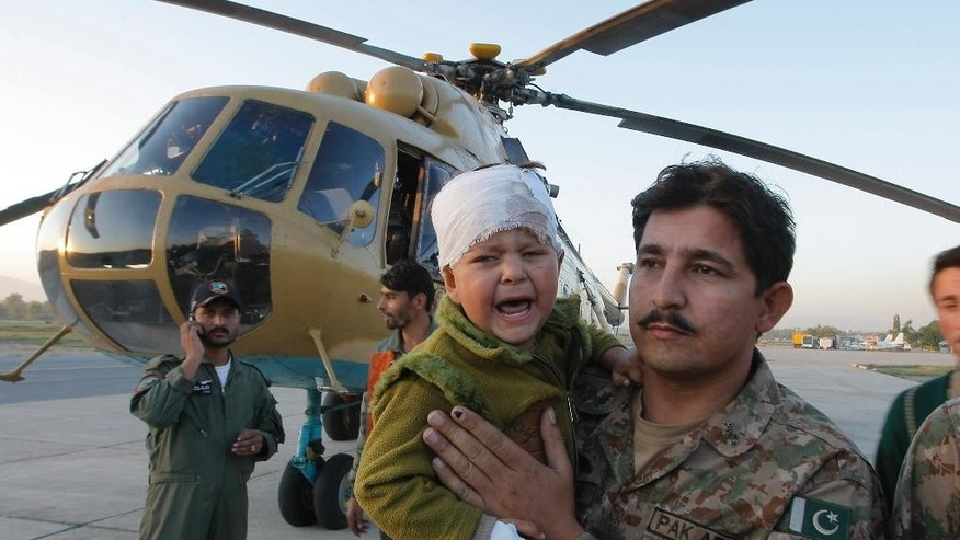 A Pakistani soldier carries an injured child who was airlifted from Chitral following Monday's deadly earthquake, at Peshawar airbase in Pakistan, Tuesday, Oct. 27, 2015. Rescuers are struggling to reach quake-stricken regions in Pakistan and Afghanistan on Tuesday as officials said the combined death toll from the previous day's earthquake rose to hundreds. (AP Photo/Mohammad Sajjad)
