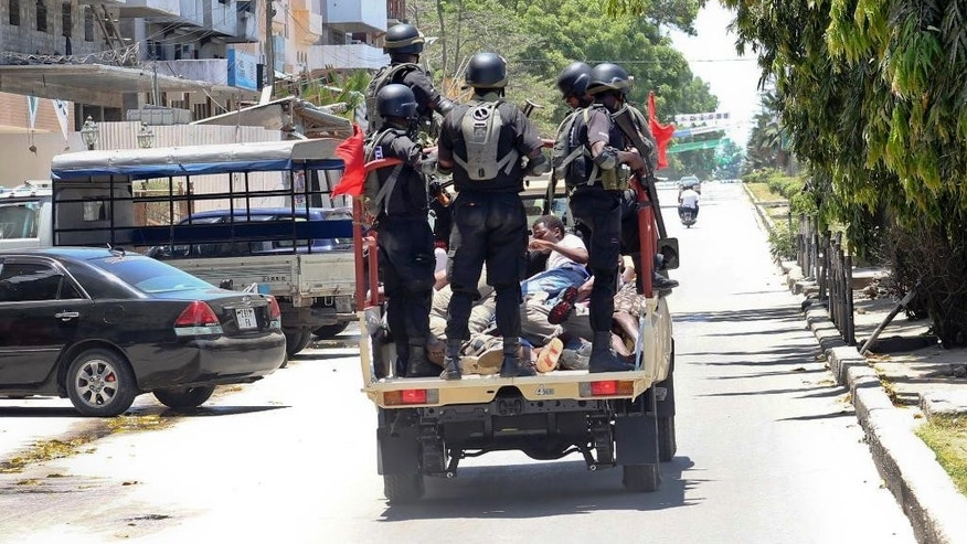 In this photo taken Monday, Oct. 26th, 2015 and made available Wednesday, Oct. 28th, 2015, police special forces ride in the back of a vehicle with unidentified men they had arrested, in the Darajani area of Stone Town, Zanzibar, a semi-autonomous island archipelago of Tanzania. Zanzibar's election commission chief announced Wednesday that the results of the island archipelago's presidential election have been nullified because of alleged irregularities, saying that the decision was taken because of several issues with the voting process, but did not say when another election would take place. (AP Photo)