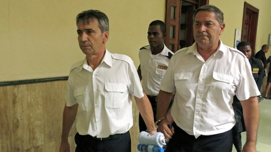 FILE - In this June 17, 2014 file photo, French pilots Bruno Odos, left, and Pascal Jean Fauret, who have been formally charged with drug trafficking, are escorted to a courtroom in Santo Domingo, Dominican Republic. The two French pilots convicted to 20 years in prison for cocaine trafficking fled house arrest and have returned to France, their lawyer says Tuesday, Oct.27, 2015. The French government insisted it didnât have anything to do with the daring and unusual escape. (AP Photo/Ezequiel Abiu Lopez, File)