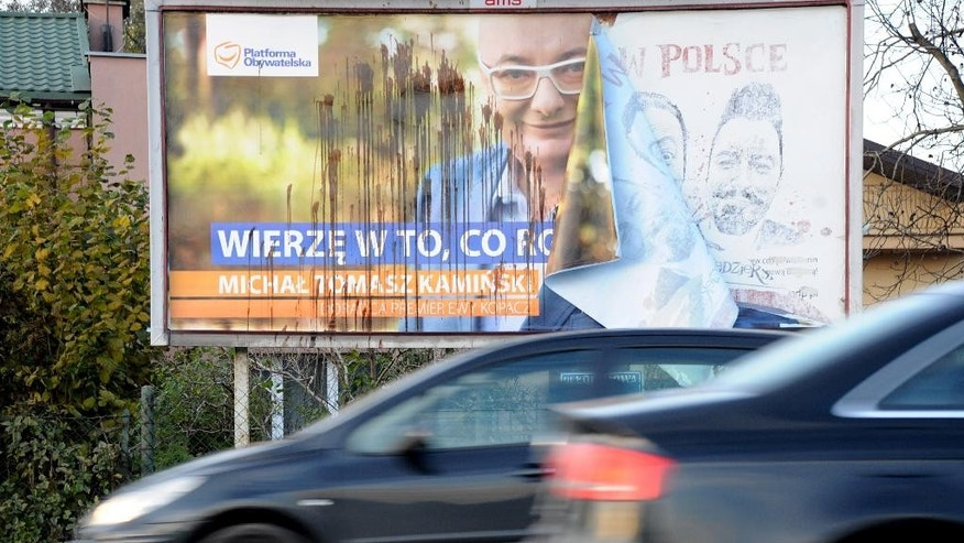 Cars drive past a damaged Civic Platform election poster in Warsaw, Poland, Monday, Oct. 26, 2015. According to an exit poll following the Sunday elections and released early Monday, the conservative Law and Justice won 37.7 percent of the votes, trouncing the governing pro-business Civic Platform, which took 23.6 percent.  (AP Photo/Alik Keplicz)