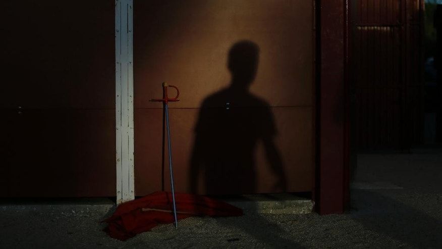 In this photo taken on Friday, Oct. 9, 2015, a youth student casts his shadow against a bullring wall next to a cape and sword at the end of a class in a bullfighting school in Madrid. A majority in the European Union's legislature wants the EU not to spend farm subsidies that could profit the raising of cattle for bullfighting. (AP Photo/Francisco Seco)